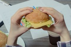 Close up photo of appetising burger in hands on a young worker a. Gainst workplace stock photos