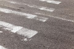 Pedestrian crossing, close-up. Close-up photo of an asphalt road on which a pedestrian crossing is partially visible Stock Photography