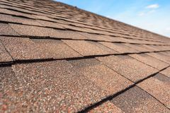 Asphalt tile roof on new home under construction. Close up photo of asphalt shingles layer on top of roof on new house under construction royalty free stock photography