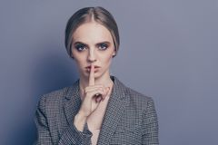 Close up photo of attractive she her lady finger close to mouth. Ask to stop talking speaking telling wearing formalwear checkered strict blazer isolated on royalty free stock photography