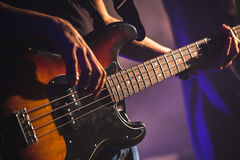 Close-up photo of bass guitar player. Hands, soft selective focus, live rock music theme Stock Photos