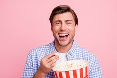 Close up photo of beautiful amazing brunet he him his handsome hold pop corn yelling of home alone movie funny moment. Wearing specs casual checkered plaid stock photography