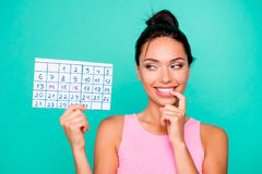 Close up photo beautiful amazing she her lady funny hairstyle bite finger hold hand arm paper calendar birthday party. Coming tricky mood wear casual pink tank stock photography