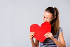 Close up photo beautiful amazing she her lady hold hands arms big large red paper heart shape figure postcard bite it. Laughter game play wear blue white royalty free stock images
