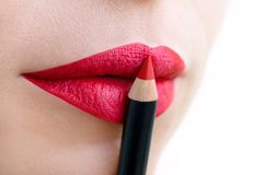 Close-up of beautiful female lips, painted in bright, saturated red color. Lip liner for both lips stock photography