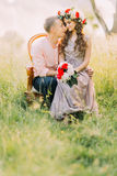 Close-up photo of beautiful smiling young couple sitting in the chair together face-to-face Royalty Free Stock Photos