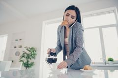 Close up photo beautiful tired she her lady pour cup hot beverage croissant inside mouth late job quickly speak tell say. Close up photo beautiful tired she her stock photo
