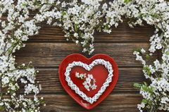Close-up photo of Beautiful white Flowering Cherry Tree branches. With red dish heart shape on vintage wooden background. Wedding, engagement or betrothal Stock Image