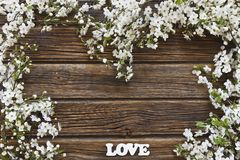 Close-up photo of Beautiful white Flowering Cherry Tree branches. With  white letters love. Wedding, engagement or betrothal concept on vintage wooden Royalty Free Stock Images