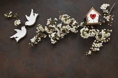 Close-up photo of Beautiful white Flowering Cherry Tree branches with two wooden birds and birdhouse. Wedding, engagement or betrothal concept on dark table Stock Images