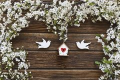 Close-up photo of Beautiful white Flowering Cherry Tree branches. With two wooden birds and birdhouse. Wedding, engagement or betrothal concept on vintage Stock Photography