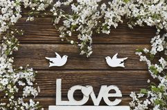 Close-up photo of Beautiful white Flowering Cherry Tree branches. With two wooden birds and letters love. Wedding, engagement or betrothal concept on vintage Stock Images