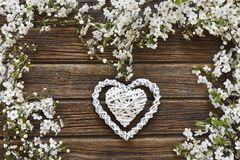 Close-up photo of Beautiful white Flowering Cherry Tree branches. With white heart shape. Wedding, engagement or betrothal concept on vintage wooden background Stock Photo