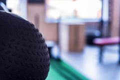 Close-up photo of black exercise ball in gym. Close-up photo with black exercise ball and blurred interior of modern gym Royalty Free Stock Image