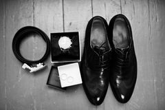 Close-up photo of black groom`s brogue shoes, watch, wedding rin. Gs, belt and bow tie on the wooden background. Black and white photo Royalty Free Stock Photo