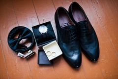 Close-up photo of black groom`s brogue shoes, watch, wedding rin. Gs, belt and bow tie on the wooden background Stock Photos