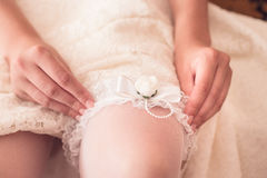 Close up photo of a bride putting tender garter on Royalty Free Stock Images