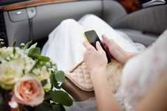 Close-up photo of bride sitting in car and holding her smartphone during her wedding day. Traffic/jam/navigation concept. Organization and control for wedding Stock Image