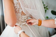 Close-up photo of bridesmaid tying bow on bridal wedding dress. Stock Photo
