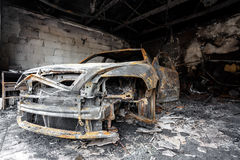 Close up photo of a burned out car. In garage after fire for grunge use Stock Images