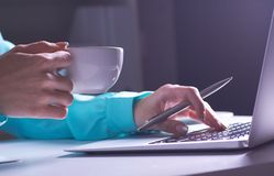 The girl is working late in the dark office with laptop. Young businesswoman girl in office. Close-up photo of a royalty free stock images