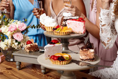 Close up photo of cakes and girls background at party. Royalty Free Stock Photo