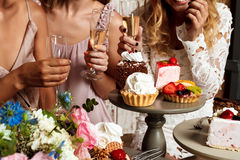 Close up photo of cakes and girls background at party. Stock Image