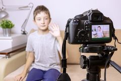 Close up photo of camera on tripod with a boy on LCD screen and blurred scene on background. Male child video blogger recording vl stock image