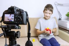 Close up photo of camera on tripod with a boy on LCD screen and blurred scene on background. Male child video blogger recording vl royalty free stock images