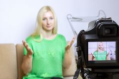 Close up photo of camera on tripod with young woman on LCD screen and blurred scene on background. Female video blogger recording. Vlog or podcast, streaming stock photography