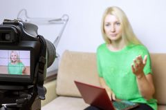 Close up photo of camera on tripod with young woman on LCD screen and blurred scene on background. Female video blogger recording royalty free stock image