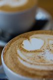 A close-up photo of a cappucino with a flat white in the background Royalty Free Stock Images