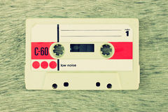 Close up photo of cassette tape over wooden table . top view. Royalty Free Stock Photos