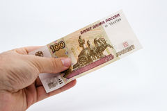 A close up photo of a Caucasian male hand holding a 100 russian ruble note.  Stock Photos