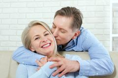 Close up photo of cheerful excited happy happily happy with toothy shining smile blond attractive woman and man, he hugs. Closeup photo of cheerful excited happy Stock Photos
