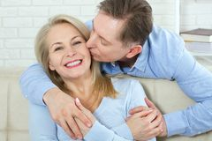 Close up photo of cheerful excited happy happily happy with toothy shining smile blond attractive woman and man, he hugs Stock Photos