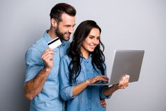 Close up photo of cheerful inspired millennial enjoying consumers shoppers using pc holding hand debit card searching royalty free stock photography