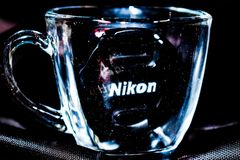 Close Up Photo Of Clear Glass Mug With Nikon Lens Cap Royalty Free Stock Images