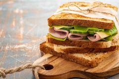 Close-up photo of a club sandwich. Sandwich with meet, prosciutto, salami, salad, vegetables, lettuce on a fresh sliced stock image