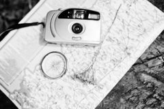 Close-up photo of compass laying on the map next to the camera. stock image