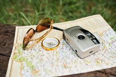 Close-up photo of compass laying on the map next to the camera a stock images