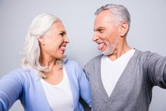 Close up photo of crazy happy mad old people, they are taking a. Selfie on a tablet, isolated on grey background stock images