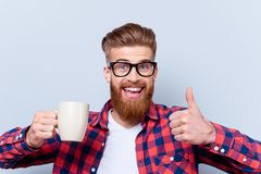 Close up photo of crazy happy smiling man in spectacles holding. Cup of tasty fresh coffee and showing thumb up royalty free stock photography