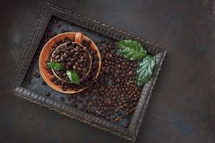 Close-up photo of cup with aroma coffee beans and fresh green leaves in frame on black table background. Top view Stock Photos