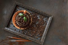 Close-up photo of cup with aroma coffee beans and fresh green leaves in frame on black table background. Top view Stock Image