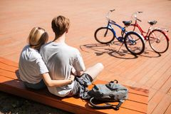 Close up photo of cute couple from back sitting on bench and embracing with backpack beside. Young man and lady spending stock photos