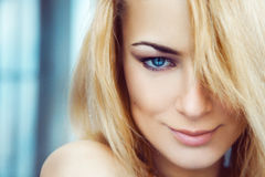 Close up photo of cute young adult blonde woman with blue eyes. Stock Images