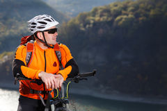 Close-up photo of cyclist in orange jacketr stands with his bike under river against beautiful landscape with mountain. Stock Photo