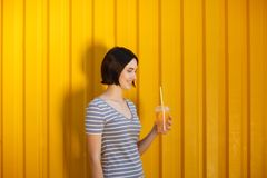A lovely and charming female holding a refreshing drink with slices of oranges on a yellow background. Healthy concept. stock image