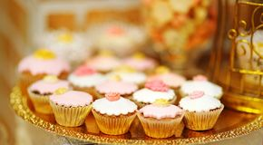 Delicious golden sweet table with cupcakes. Close up photo of delicious golden sweet table with cupcakes royalty free stock image